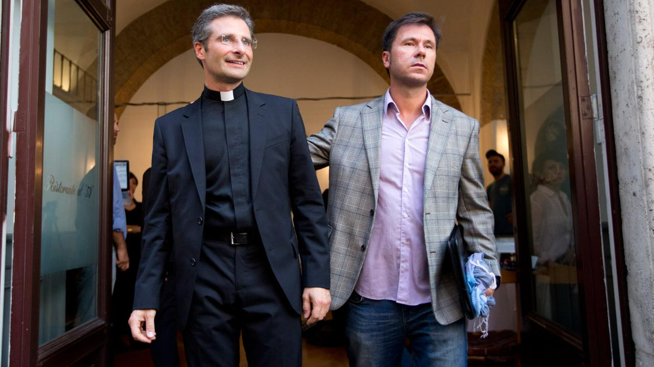 Monsignor Krzysztof Charamsa and his boyfriend Eduard pose for a photo as they leave a restaurant after a news conference in downtown Rome, Saturday Oct. 3, 2015.