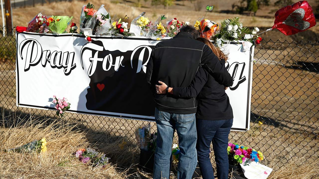 Charley Thompson, left, and his wife Rachel Thompson embrace as they place flowers at a makeshift memorial near the road leading to Umpqua Community College, Saturday, Oct. 3, 2015, in Roseburg, Ore.