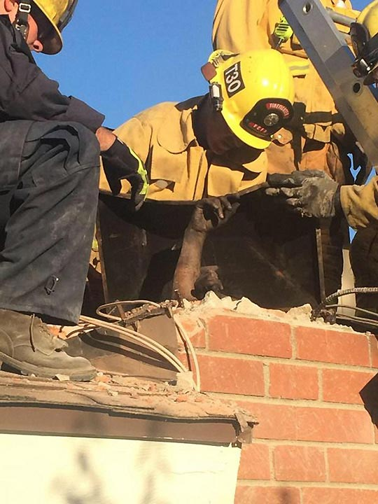 <div class='meta'><div class='origin-logo' data-origin='none'></div><span class='caption-text' data-credit='VCFD Capt. Mike Lindbery, Twitter.com/VCFD_PIO'>A woman reaches out as USAR members rescue her from a chimney in Thousand Oaks on Sunday, Oct. 19, 2014.</span></div>