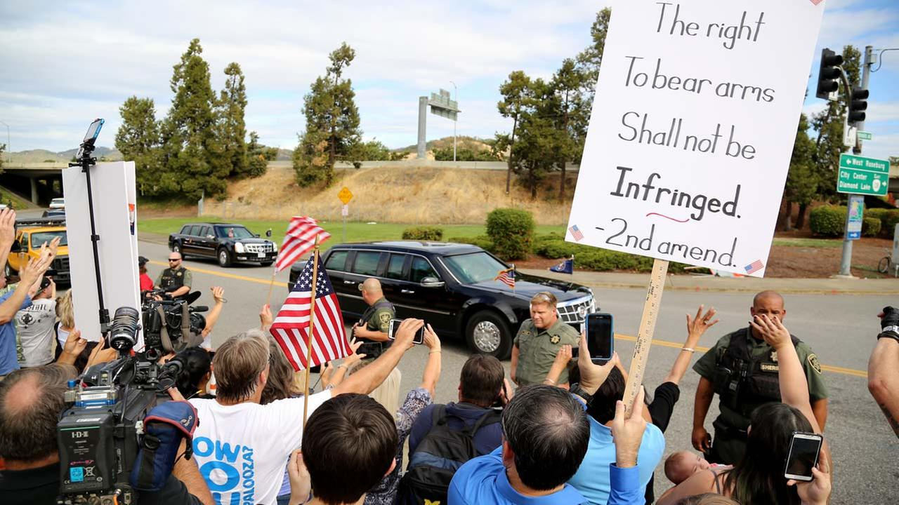 Demonstrators watch as President Barack Obamas motorcade leaves Roseburg High School after a visit with families of victims of the shootings at Umpqua Community College in Roseburg, Ore., Friday, Oct. 9, 2015.