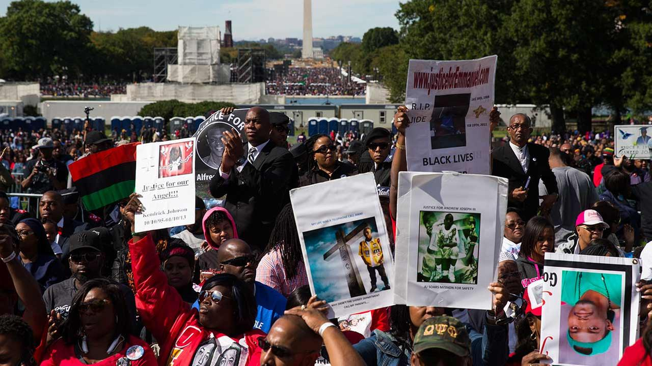 People cheer during a rally to mark the 20th anniversary of the Million Man March, on Capitol Hill, on Saturday, Oct. 10, 2015, in Washington.