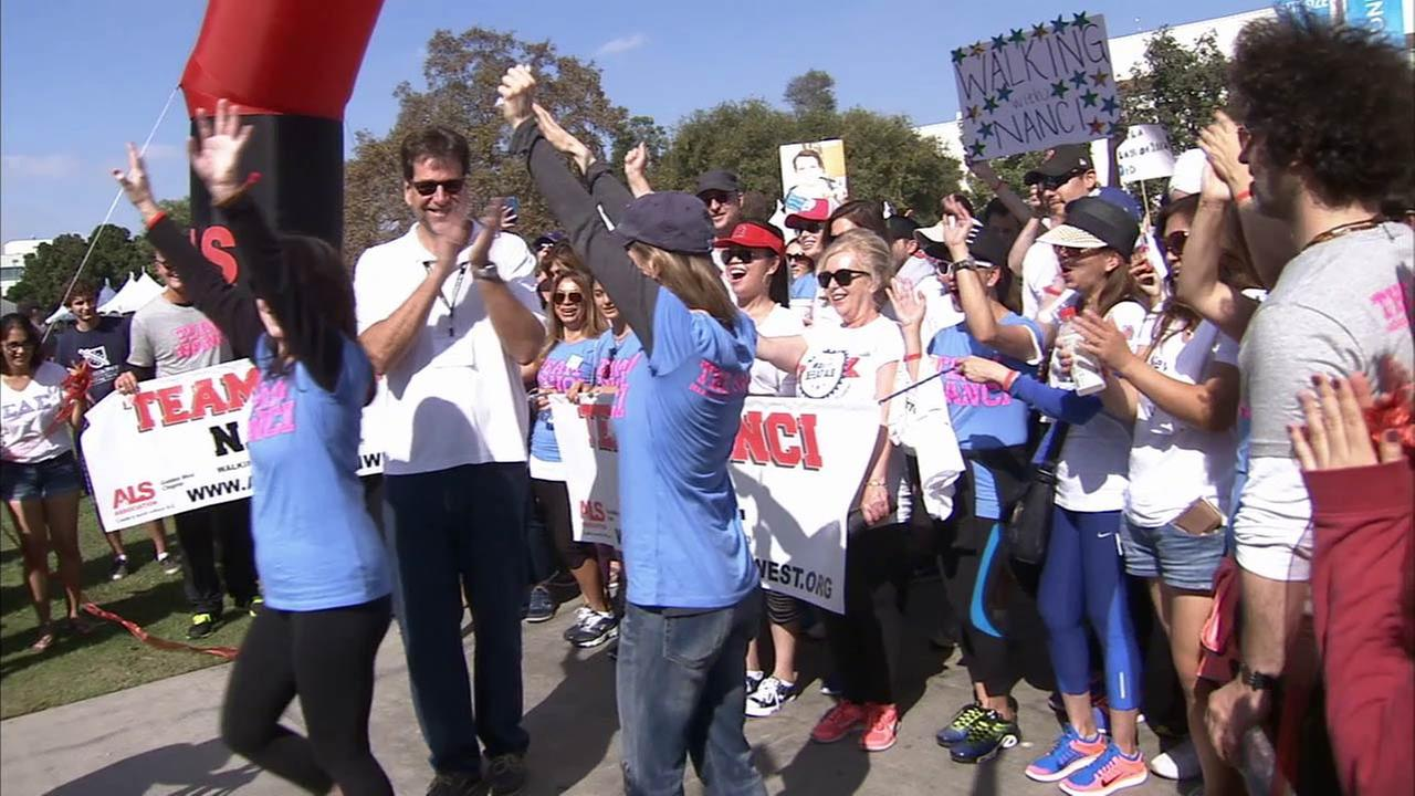 Participants at an annual Walk to Defeat ALS are seen celebrating after the kick off.
