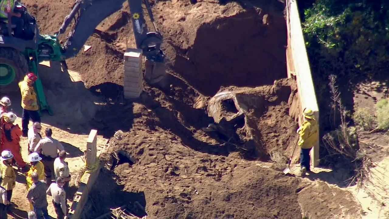 Fire officials are seen digging up a car found 6 feet deep in dirt in Palmdale Tuesday, Oct. 20, 2015, after a previous storm that caused severe mud flow days before.