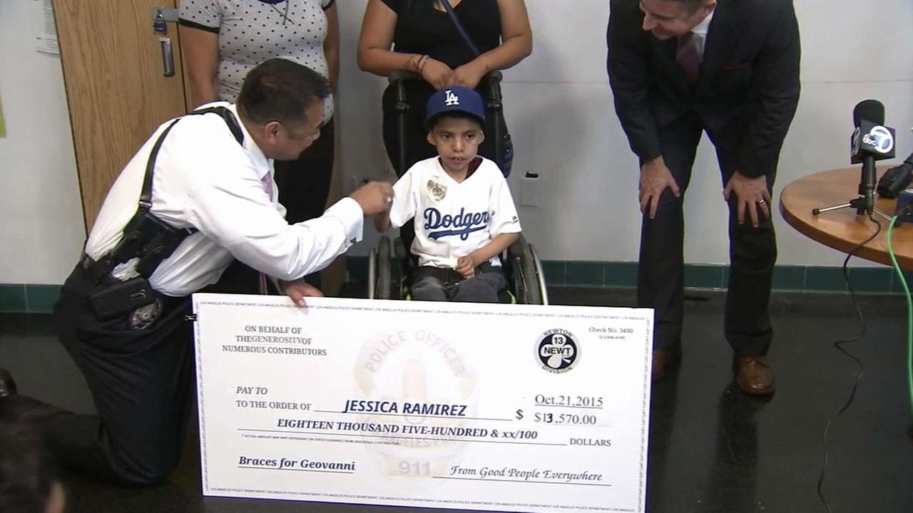 Geovanni Ramirez smiles for photos and shakes an LAPD officers hand as he receives a more than $13,000 check and new leg braces on Thursday, Oct. 22, 2015.