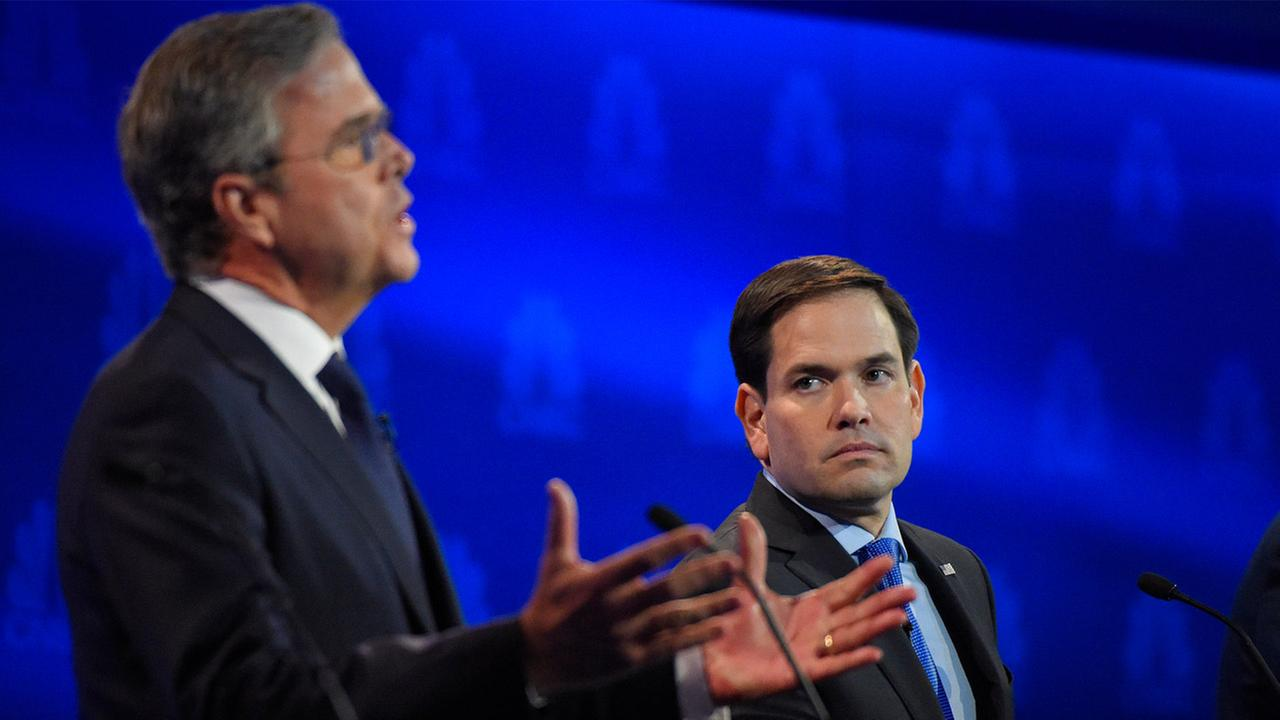 Marco Rubio, right, watches as Jeb Bush speaks during the CNBC Republican presidential debate at the University of Colorado, Wednesday, Oct. 28, 2015, in Boulder, Colo.