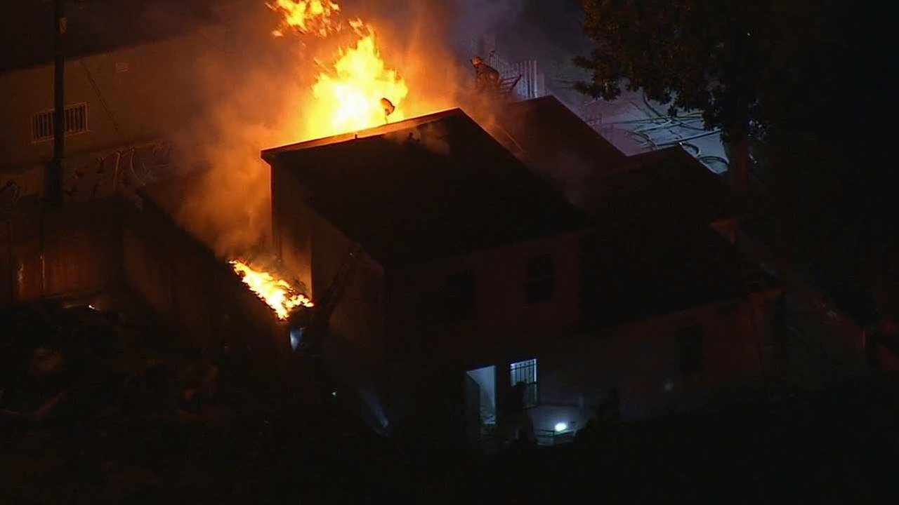 Los Angeles firefighters battle a house fire near S. Vermont Ave and W. 74th St in the Vermont Knolls area of South L.A. on Friday, Oct. 30, 2015.