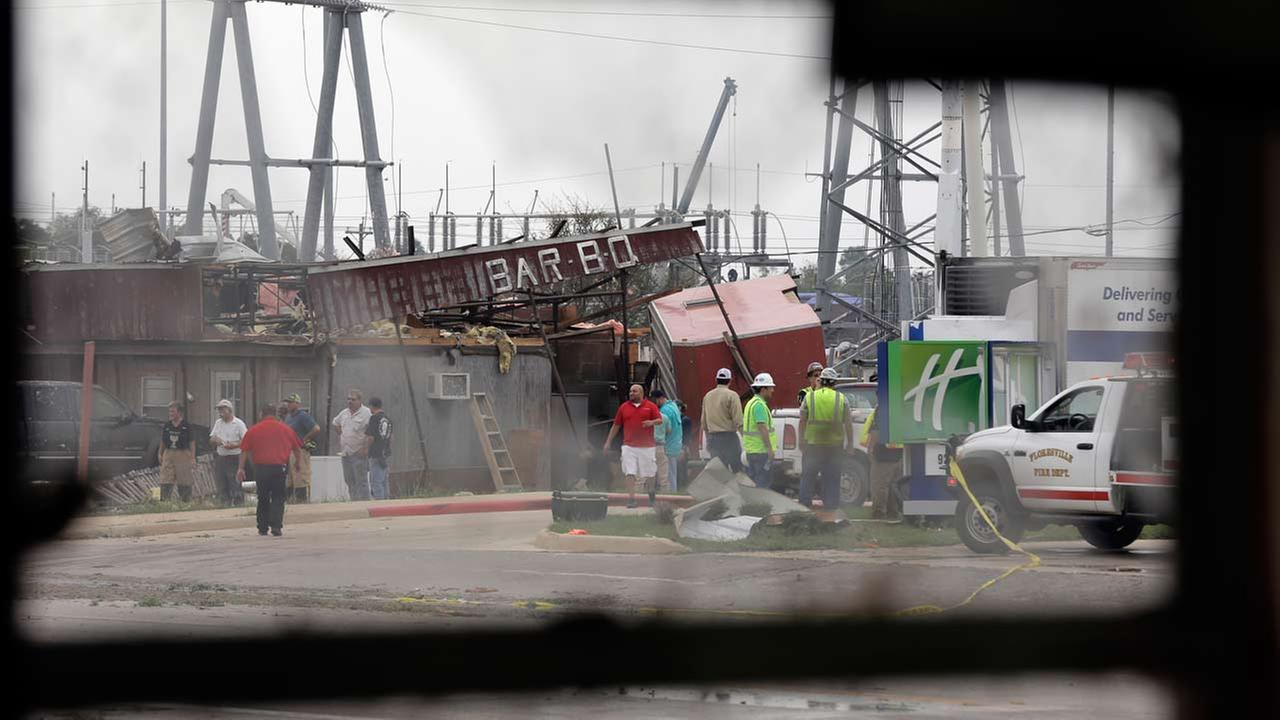 A business damaged by a tornado is seen through the window of another business also hit by the twister, Friday, Oct. 30, 2015, in Floresville, Texas.