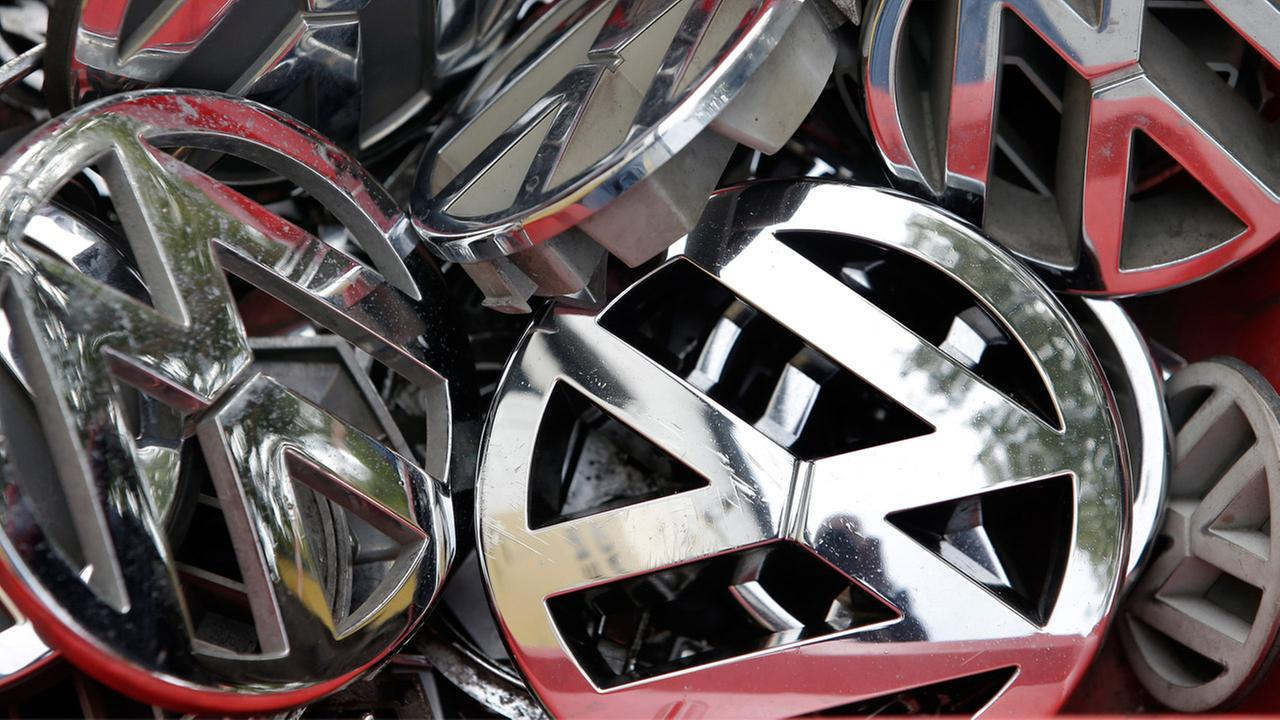In this Sept. 23, 2015 file photo, company logos of the German car manufacturer Volkswagen sit in a box at a scrap yard in Berlin, Germany.