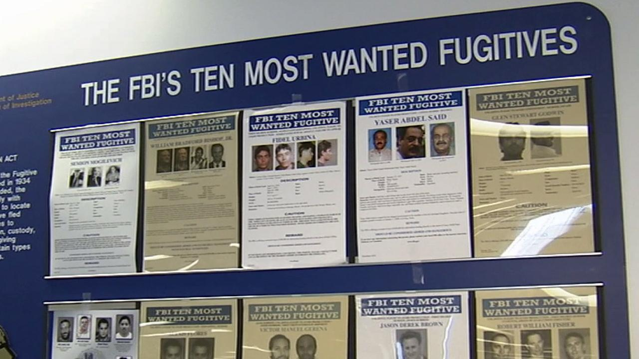 Posters of the top 10 most wanted fugitives in the FBI hangs on a wall in an undated photo.