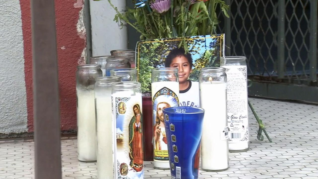A memorial filled with flowers and candles sits on the stoop of an apartment building in the Pico-Union neighborhood where a 14-year-old boy was killed.