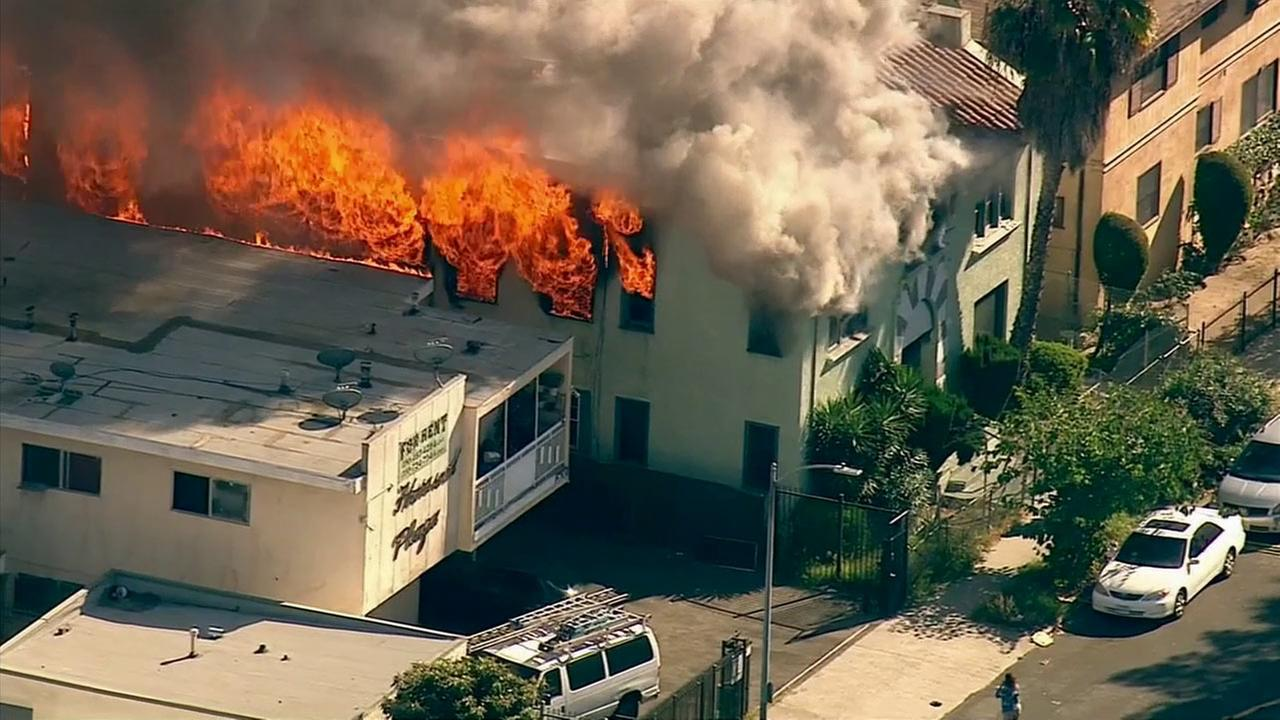 Flames shoot out from a building on 2600 block of Harvard Boulevard in South Los Angeles on Tuesday, Nov. 10, 2015.