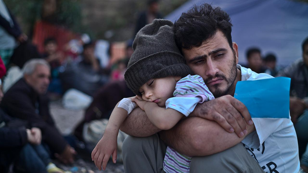 In this Sunday, Oct. 4, 2015 file photo, a Syrian refugee child sleeps in his fathers arms after arriving on a dinghy from the Turkish coast to the Greek island of Lesbos.
