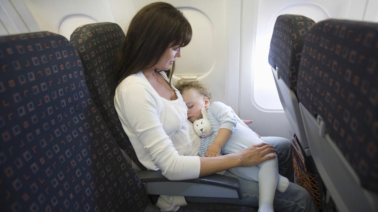 A baby sleeps on mothers lap while in an airplane in this undated file photo.