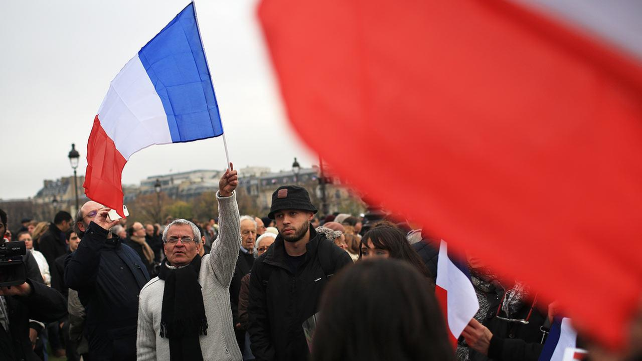 People holding French flags gather outside the Invalides, during a ceremony honoring those killed in the Nov. 13 attacks, in Paris, Friday, Nov. 27, 2015.