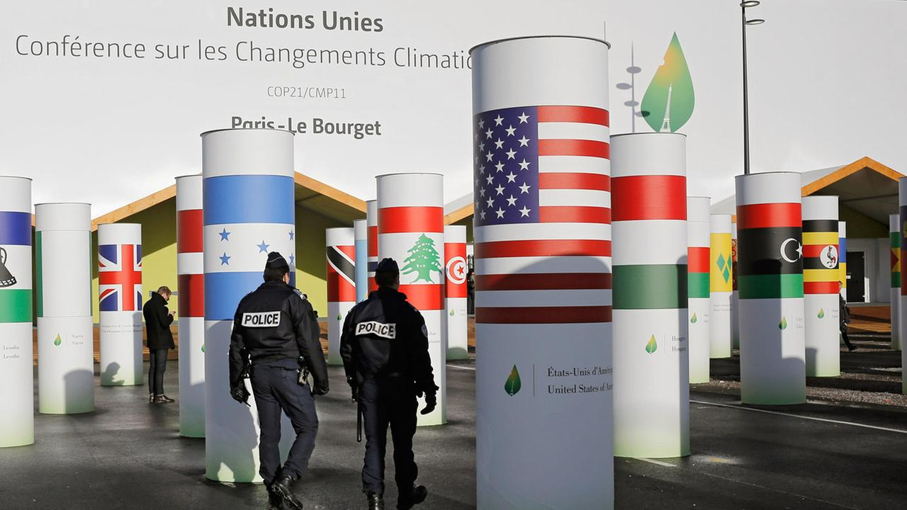 Policemen patrol outside the main entrance of the United Nations Climate Change Conference in Le Bourget, outside Paris, Saturday, Nov. 28, 2015.