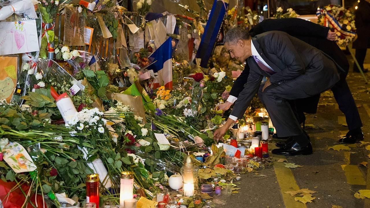 U.S. President Barack Obama, right, and French President Francois Hollande pay their respect at the Bataclan concert hall, one of the recent deadly Paris attack sites.