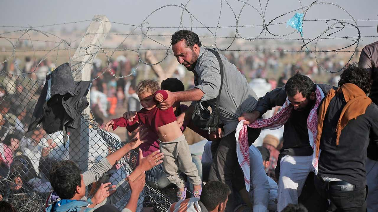 In this Sunday, June 14, 2015 file photo, a Syrian refugee carries a baby over the broken border fence into Turkey after breaking the border fence and crossing from Syria in Akcakale, Sanliurfa province, southeastern Turkey.