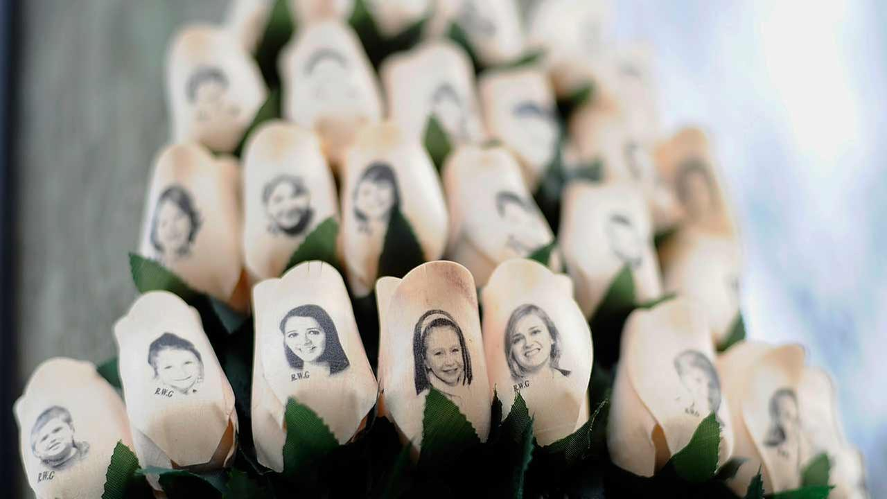In this Jan. 14, 2013 file photo, white roses with the faces of victims of the Sandy Hook Elementary School shooting are attached to a telephone pole near the school on the one-month anniversary of the shooting that left 26 dead in Newtown, Conn.