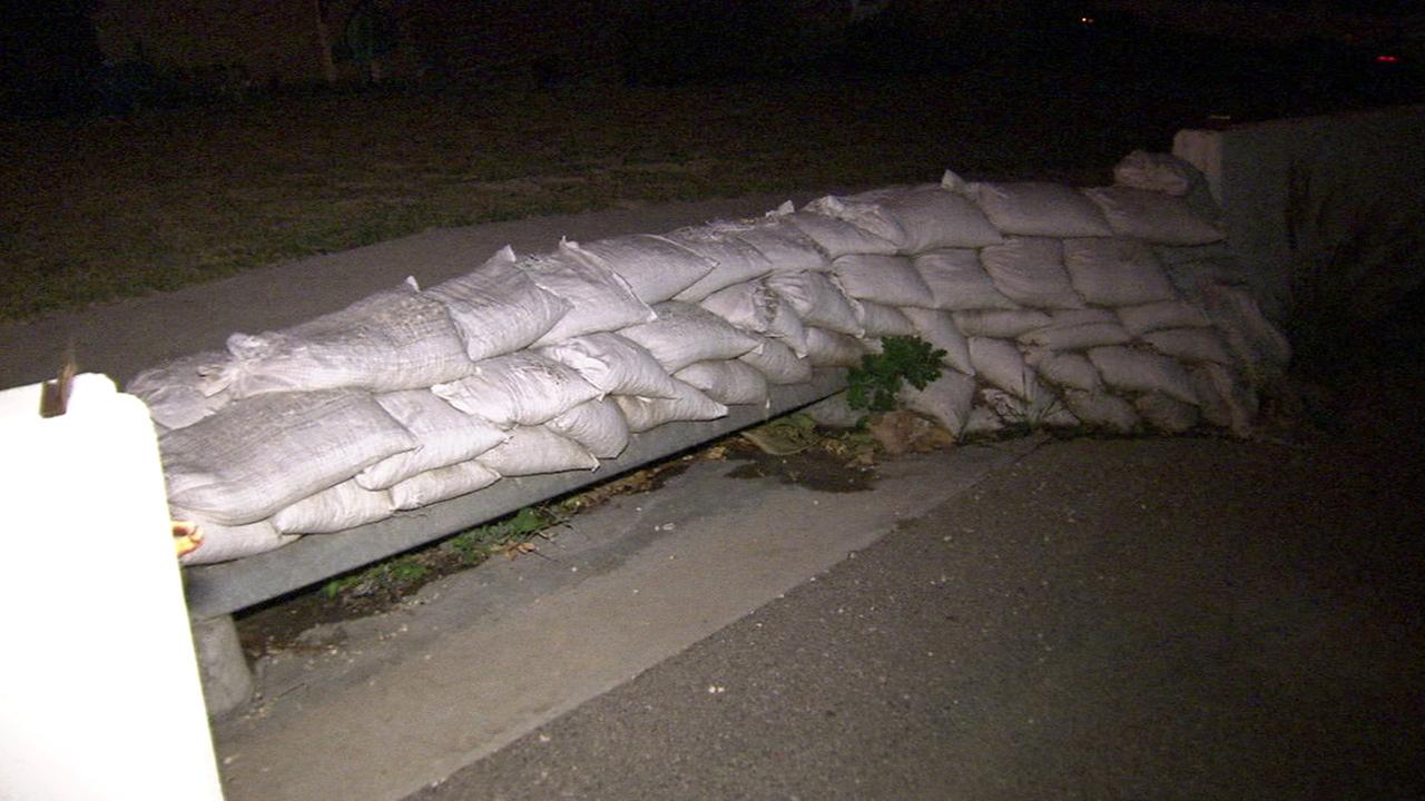 Residents in a Los Angeles neighborhood prepare sandbags near storm drains on Sunday, Jan. 3, 2016.