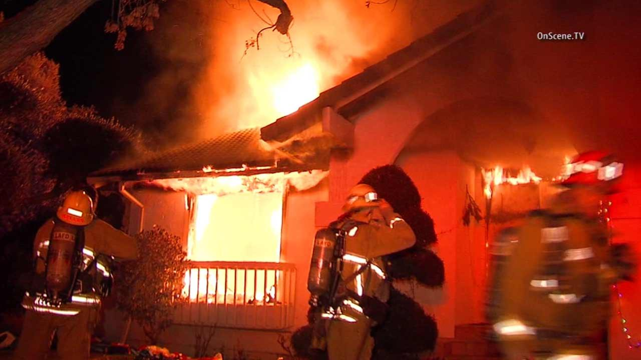 Los Angeles firefighters battle a blaze at a two-story home in the 17000 block of W. Blackhawk Street in Granada Hills on Monday, Jan. 4, 2015.