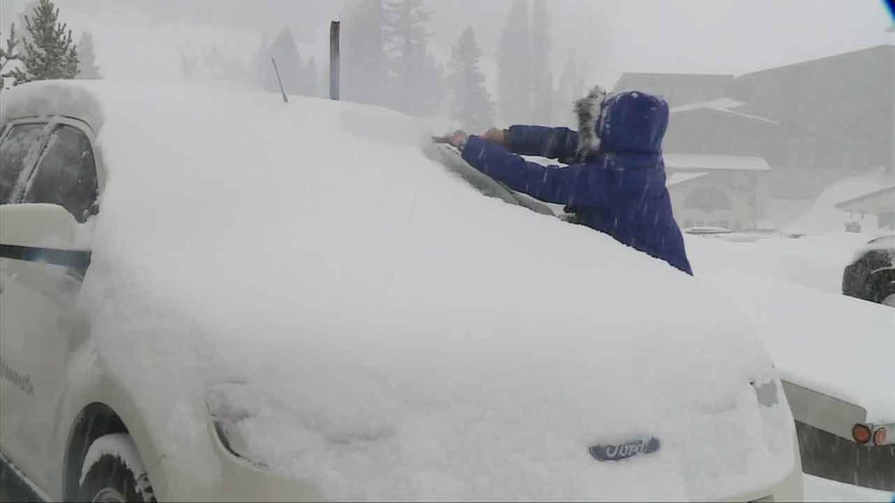 A woman wipes a thick layer of snow off her car in Mammoth Mountain on Tuesday, Jan. 5, 2016.