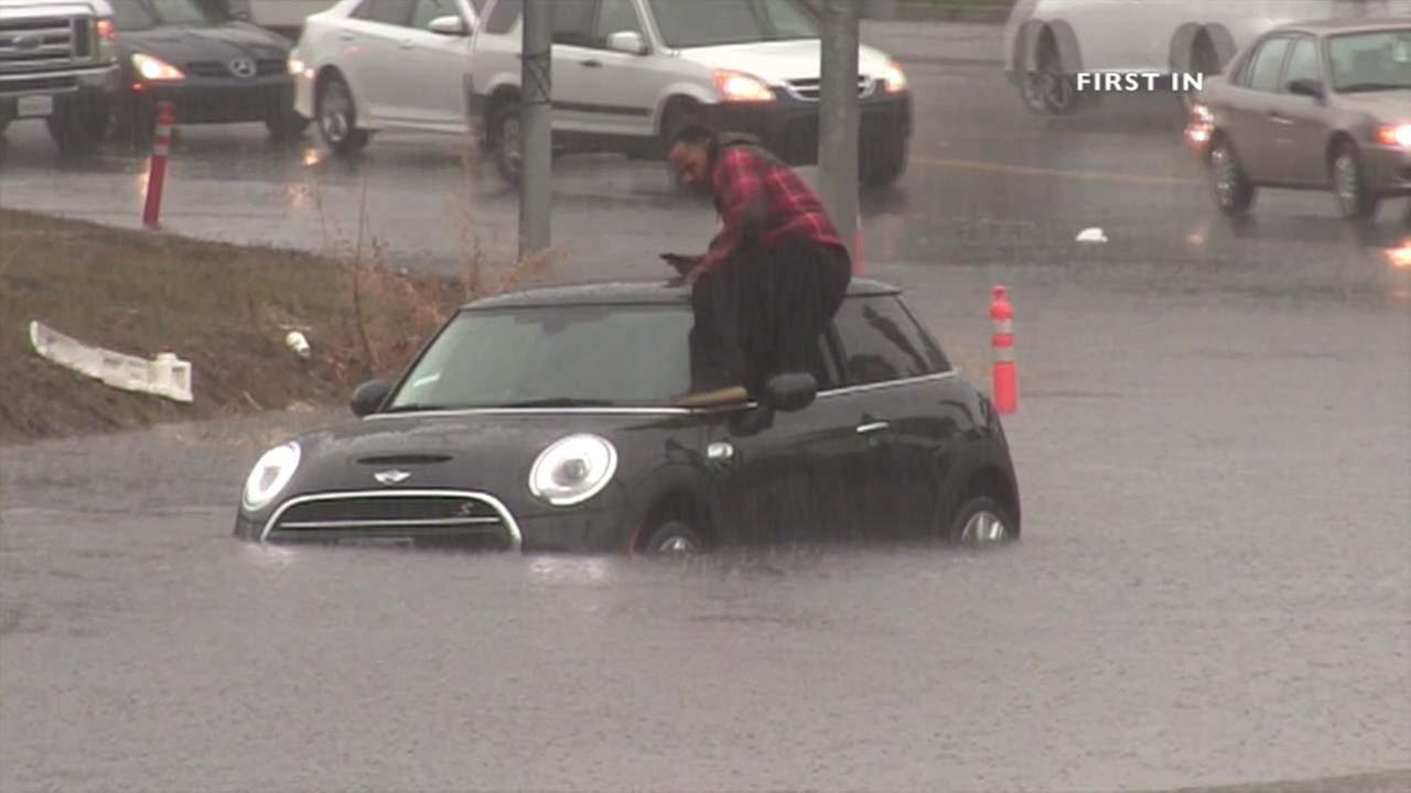 A man climbs out of his car and jumps to safety after flood waters overtake a street near the Sepulveda Basin on Tuesday, Jan. 5, 2016.KABC