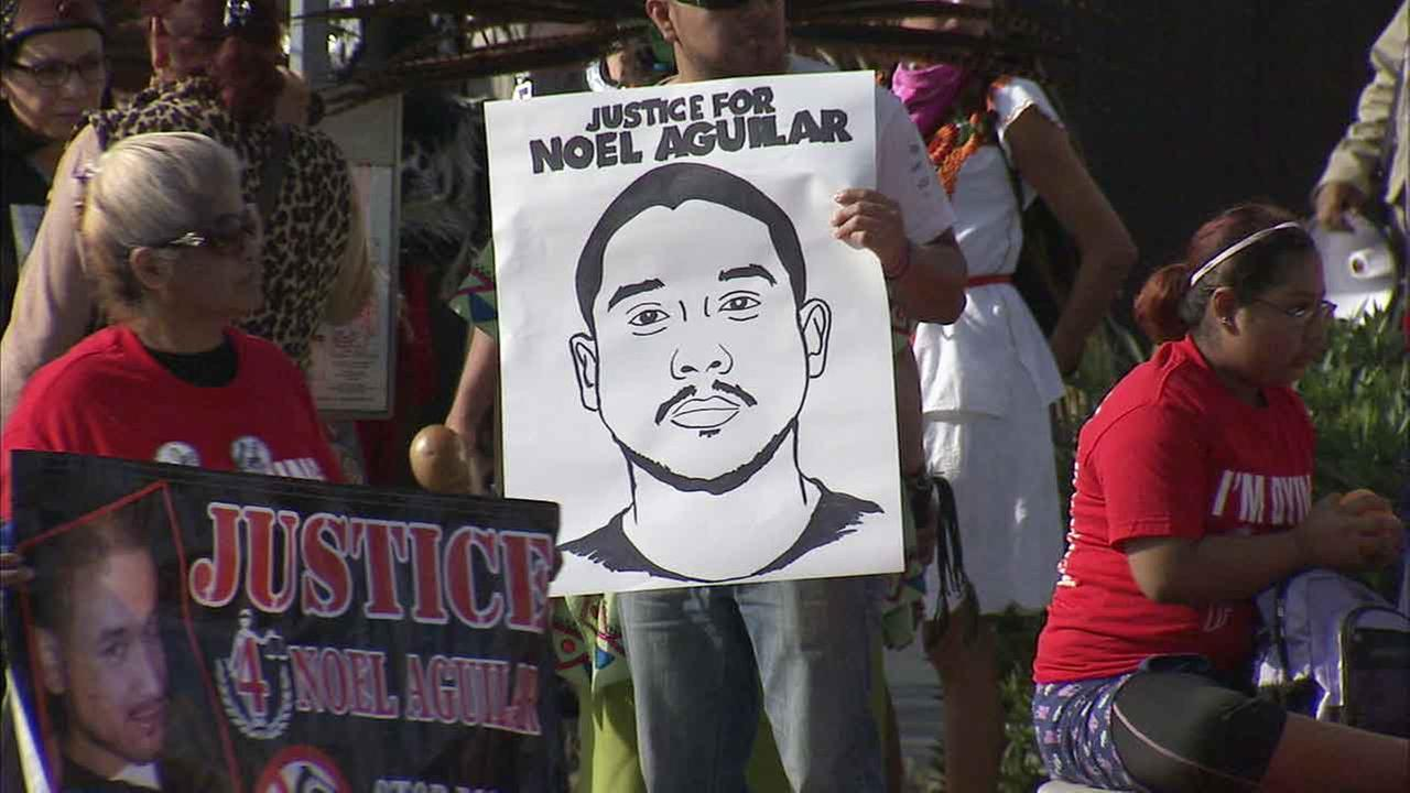 Dozens of protesters voice their outrage on Saturday, Jan. 16, 2016, over the 2014 fatal shooting of Noel Aguilar in Long beach, Calif.
