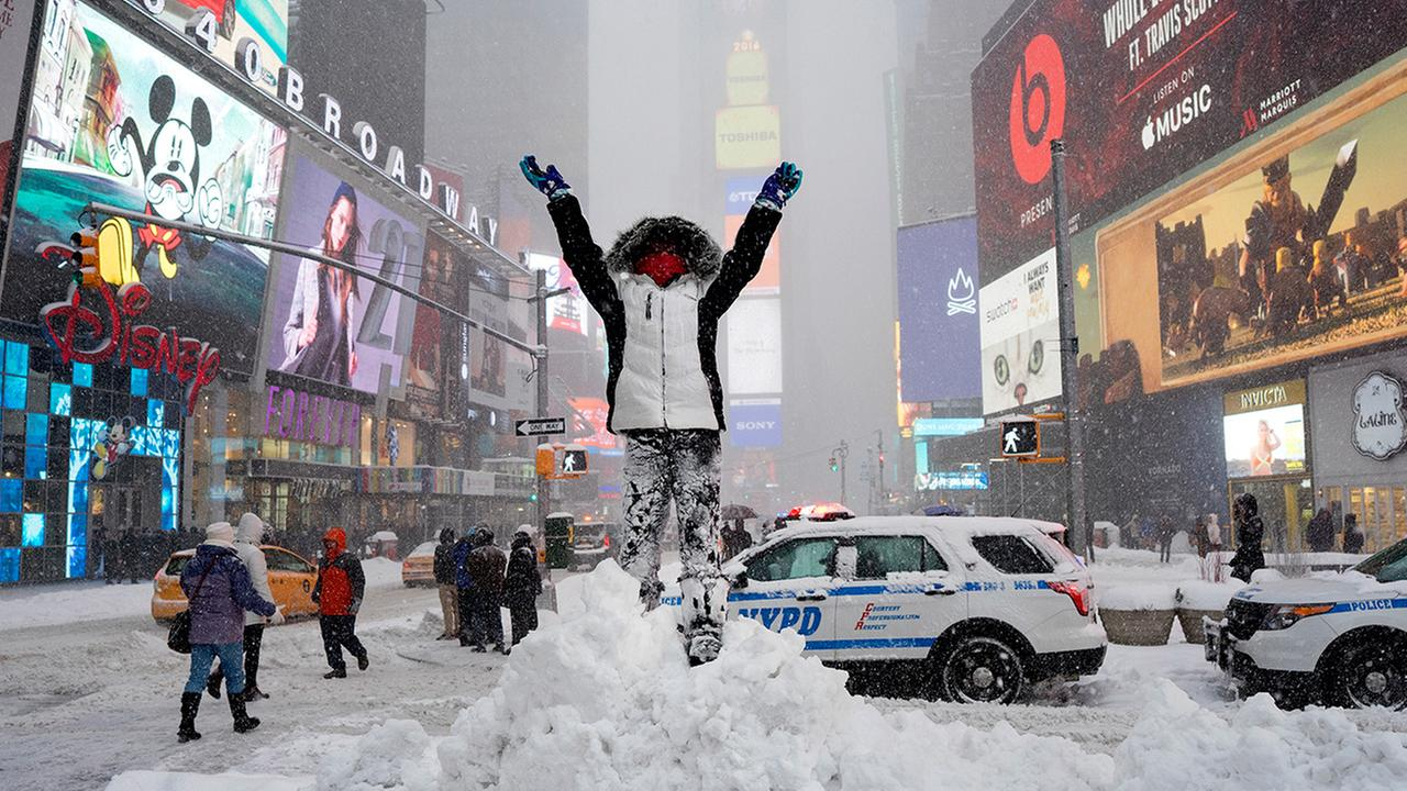 Bella Fraker stands on a snow pile as she poses for a family photo in New Yorks Times Square, Saturday, Jan. 23, 2016, as a large winter storm rolls up the East Coast.