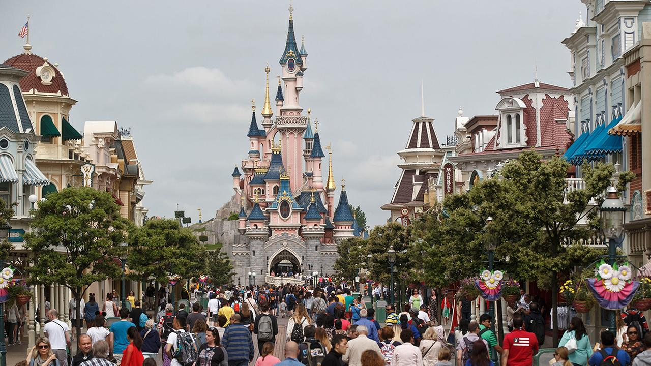 In this undated file photo, visitors walk toward the Sleeping Beautys Castle, background, at Disneyland Paris in Chessy, France, east of Paris.