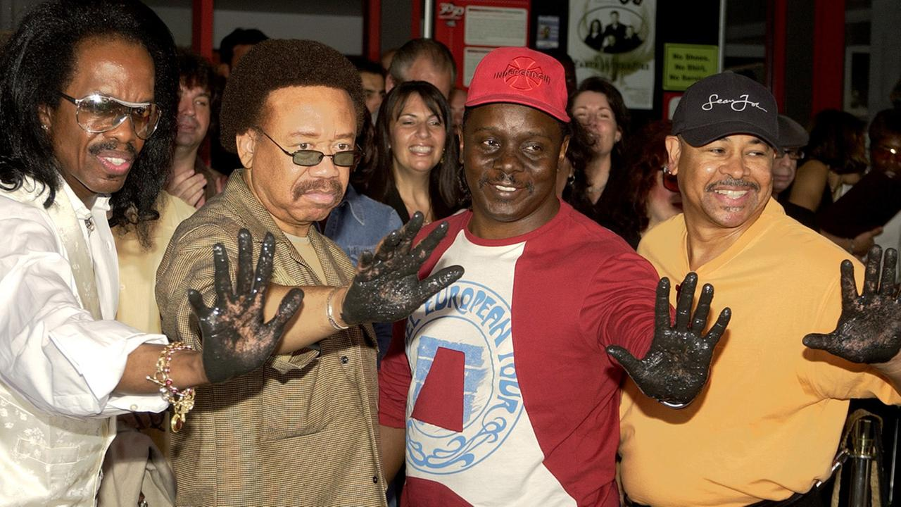 Earth, Wind and Fire members, left to right, Verdine White, Maurice White, Philip Bailey, and Ralph Johnson hold up their hands after leaving imprints at the Hollywood Rock Walk.