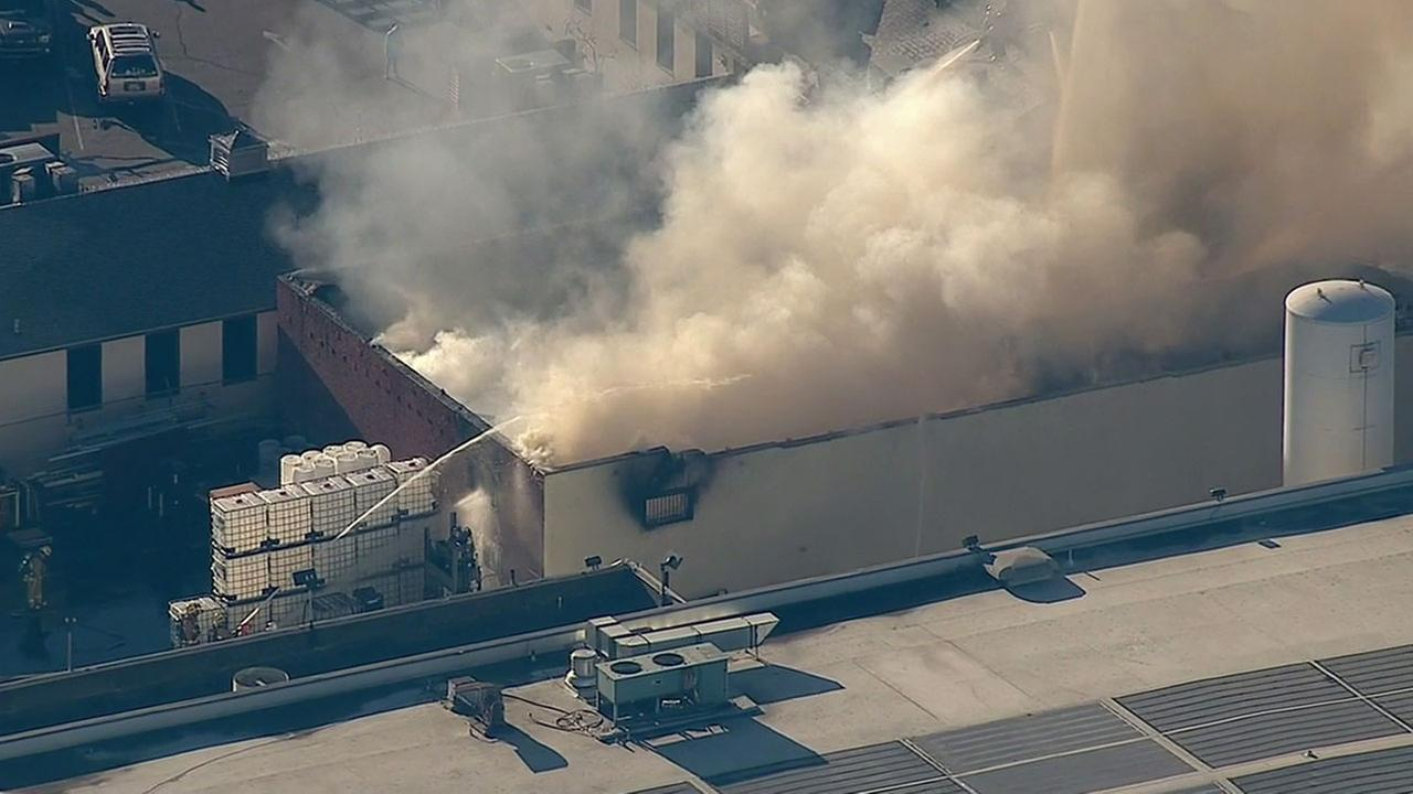 Firefighters work to put out a fire the burned through the roof of an industrial building in downtown Los Angeles on Tuesday, Feb. 9, 2016.