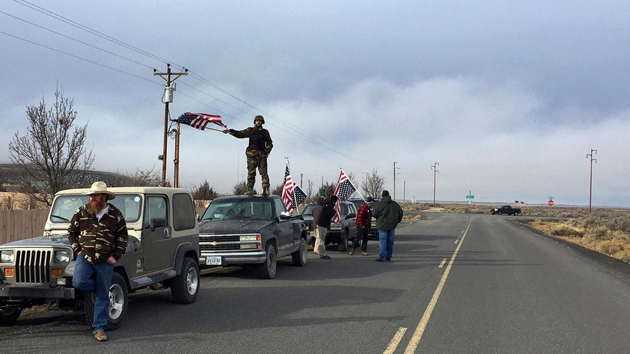 People wave American flags outside the Oregon wildlife refuge where the last occupiers surrendered Feb. 11, 2016.