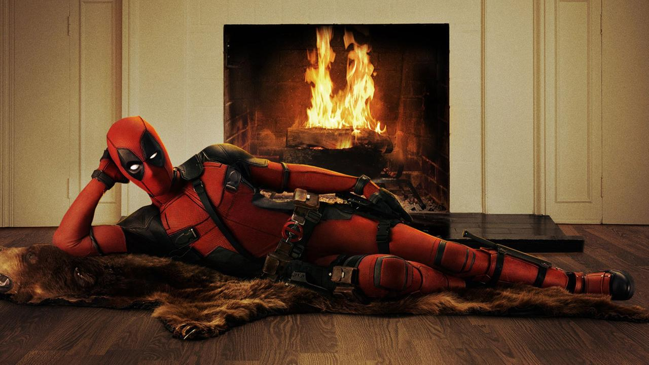 Deadpool is shown posing by a fireplace in a promotional photo for the movie.