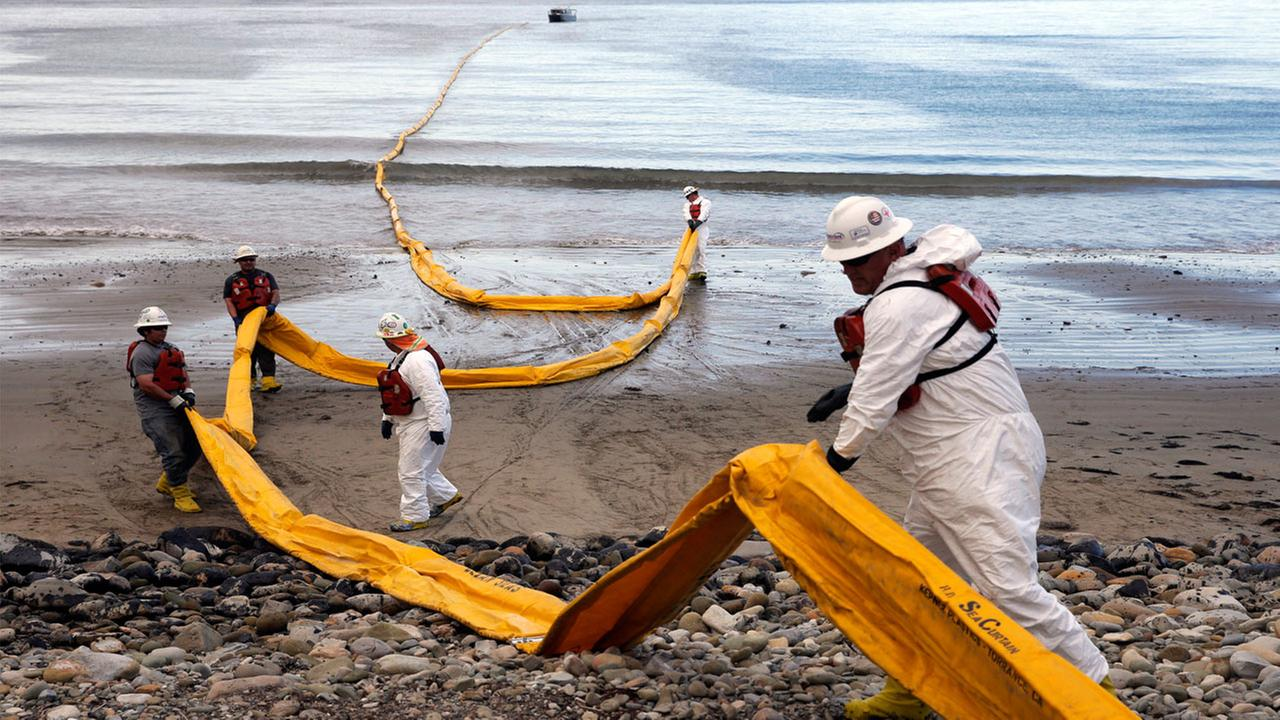 In this May 21, 2015 photo, workers prepare an oil containment boom at Refugio State Beach, north of Goleta, Calif.