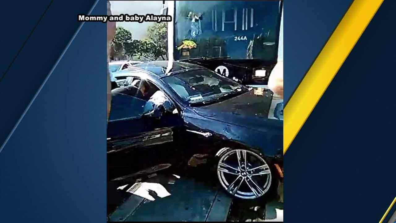 Witnesses help a trapped driver who survived being struck by a Metro Blue Line train in downtown Los Angeles on Sunday, Feb. 21, 2016.