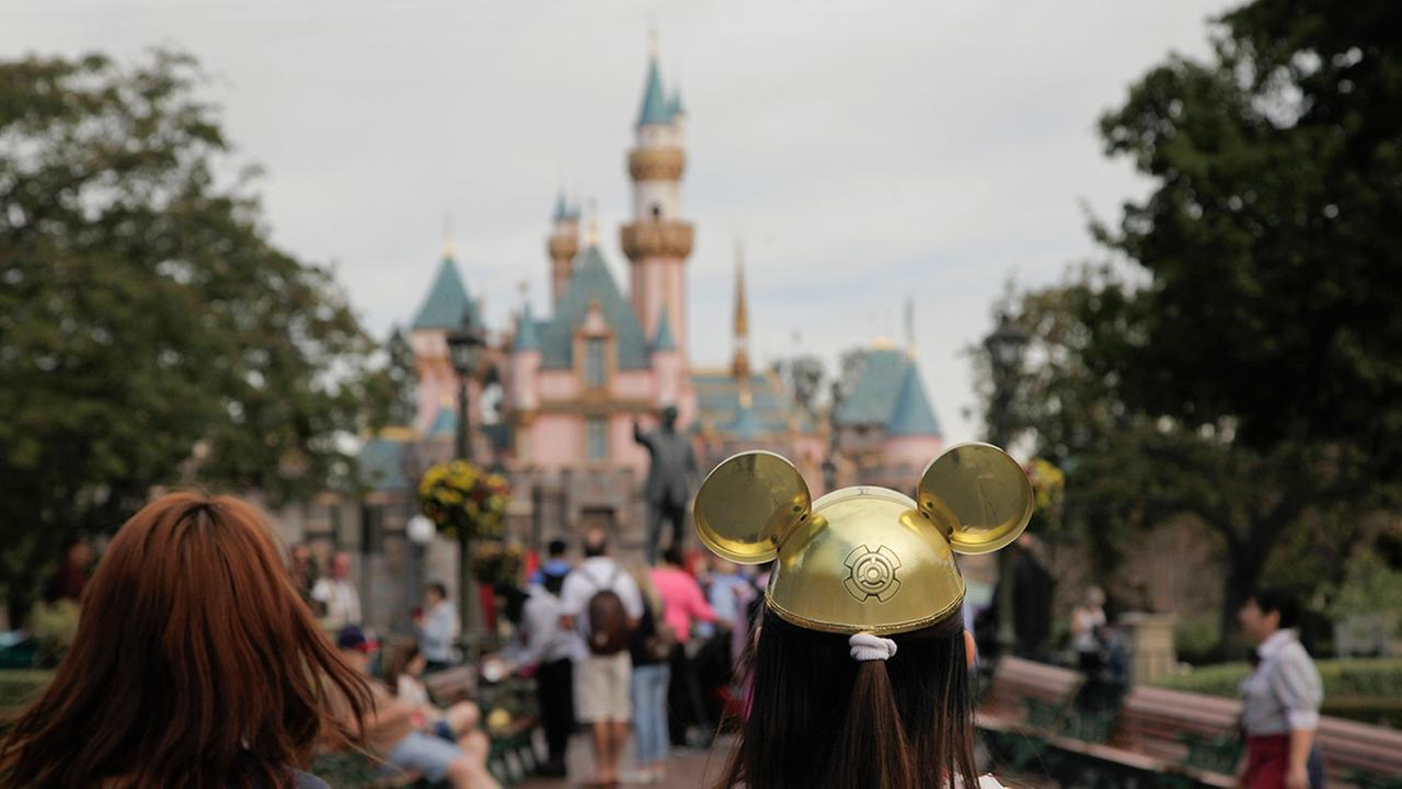 FILE - In this Jan. 22, 2015, file photo, a woman with a Mickey Mouse hat walks toward Sleeping Beautys Castle at Disneyland, in Anaheim, Calif.