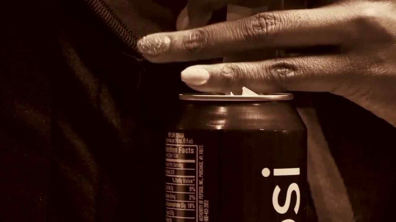 A generic image of a person spiking a soda drink.