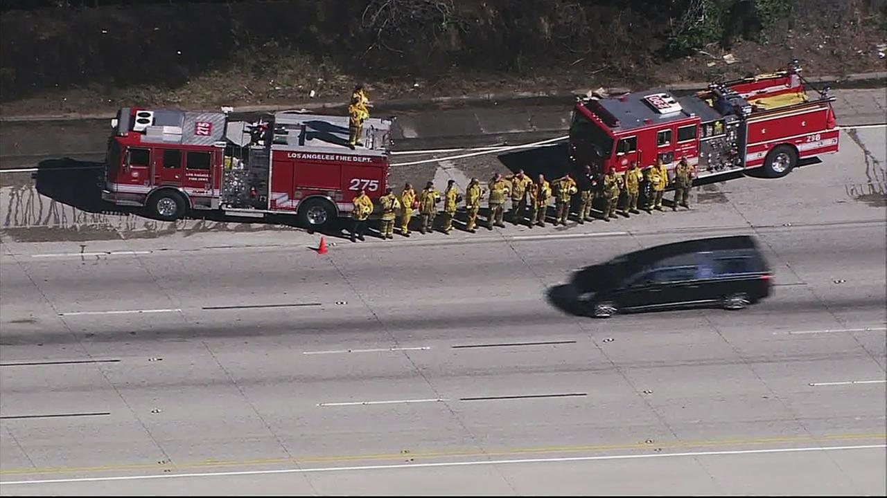 Firefighters salute as the hearse carrying former first lady Nancy Reagans casket drives by on Wednesday, March 9, 2016.KABC