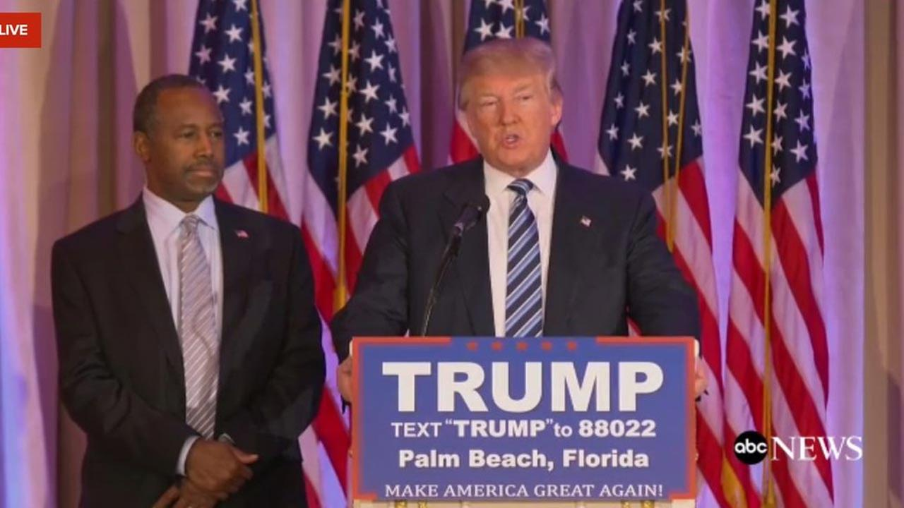 Ben Carson stands behind Donald Trump during a campaign event where Carson announced that he is endorsing the GOP front-runner for president.
