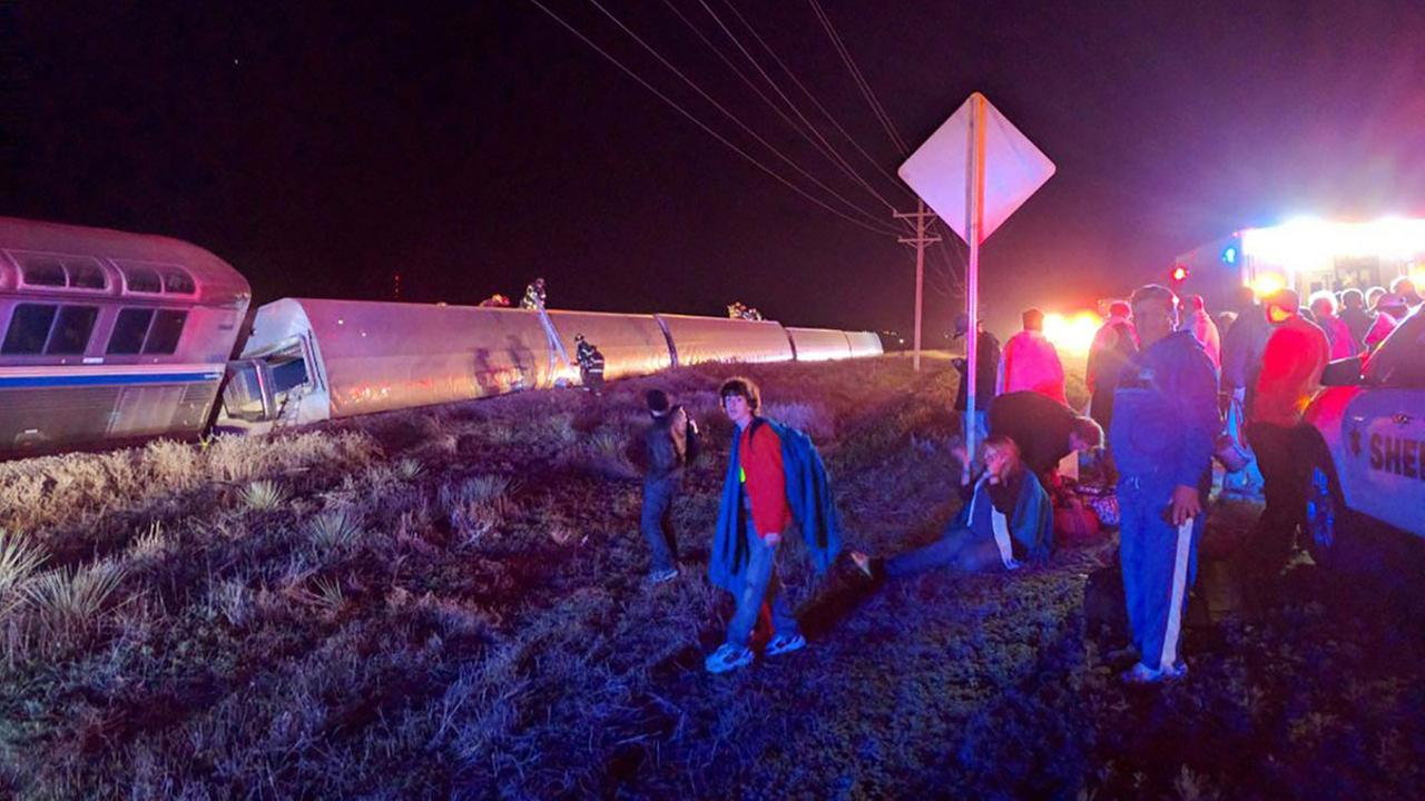 Passengers gather after a train derailed near Dodge City, Kan., Monday, March 14, 2016.