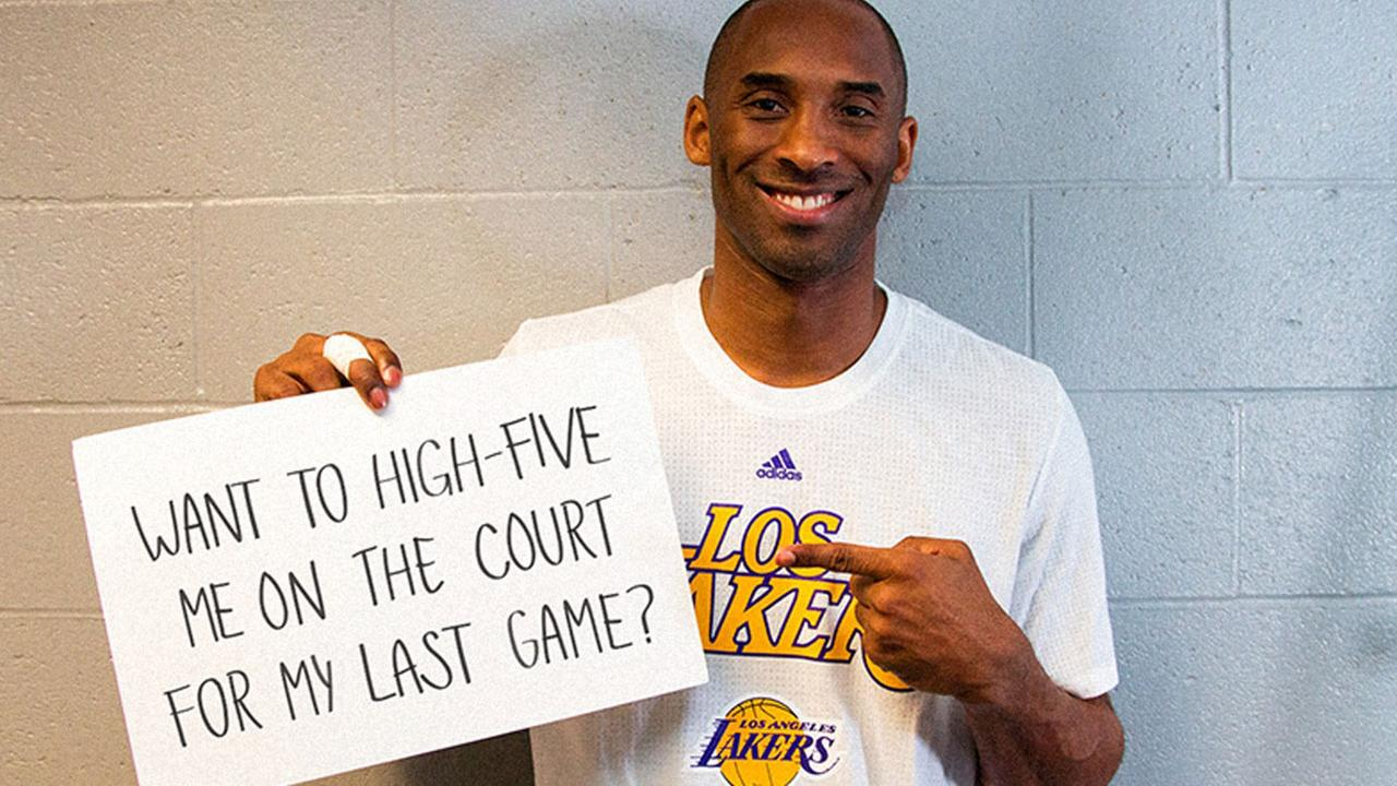 Kobe Bryant holds up a sign as part of a donation contest where fans have a chance to win courtside seats to his last game.