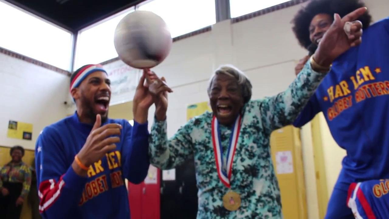 Virginia McLaurin, 107, learns to spin the ball thanks to Moose Weekes and Zeus McClurkin from the Harlem Globetrotters.