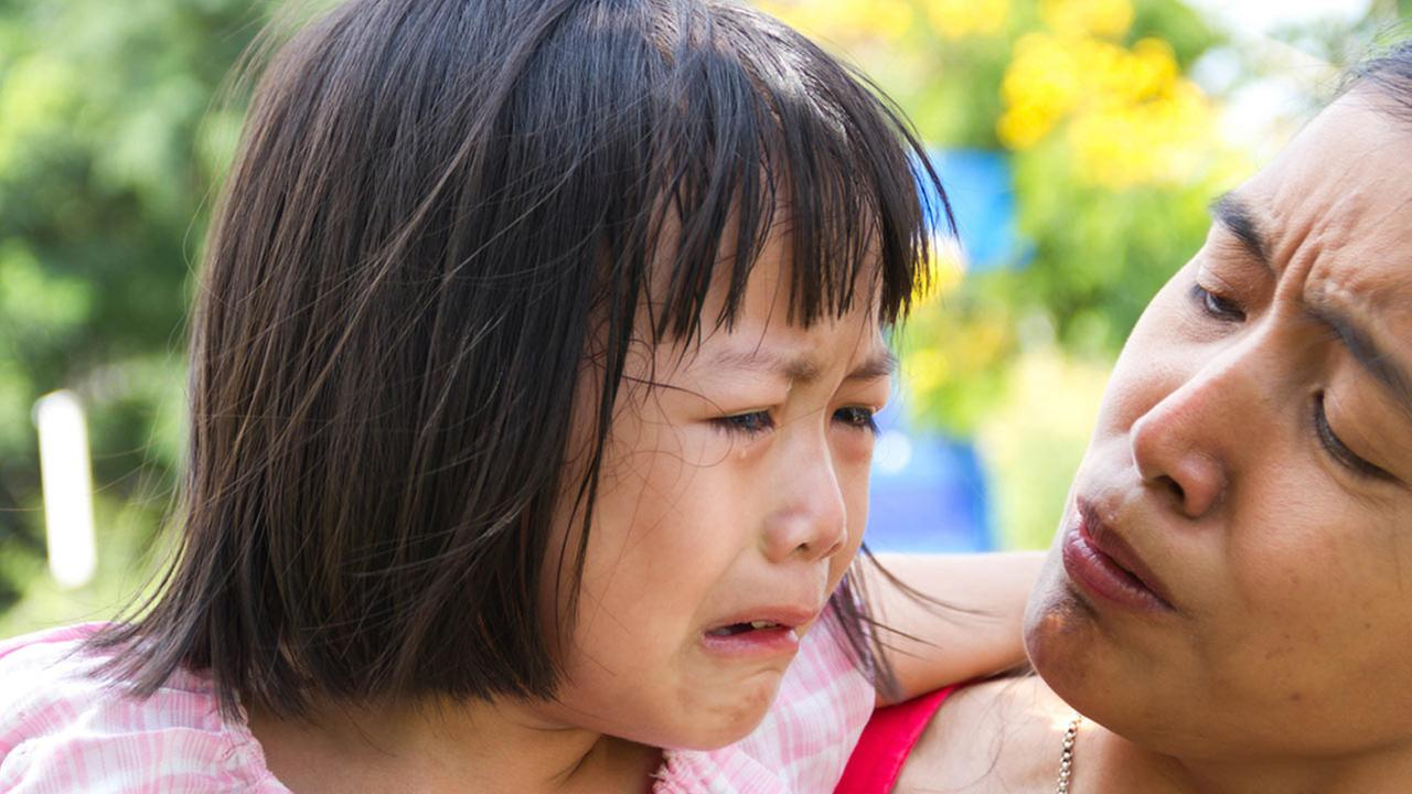 A mother tries to comfort her crying daughter in this file photo.