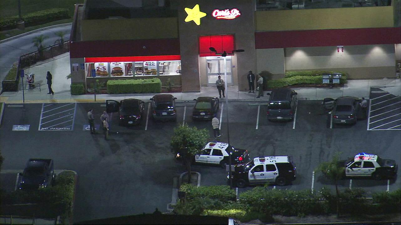 Law enforcement officials investigate the scene of a shooting at a Carls Jr. restaurant in Compton on Thursday, March 18, 2017.