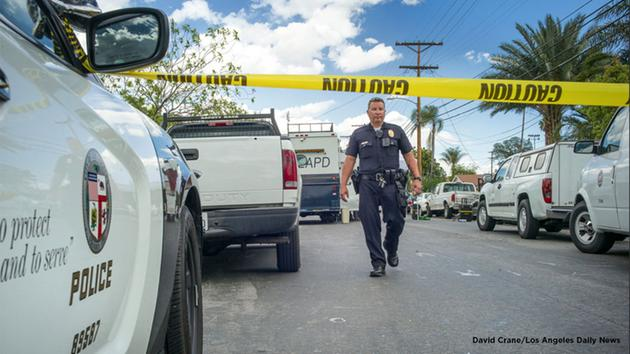 Los Angeles police investigate a fatal shooting and stabbing in North Hills Tuesday, March 29, 2016.
