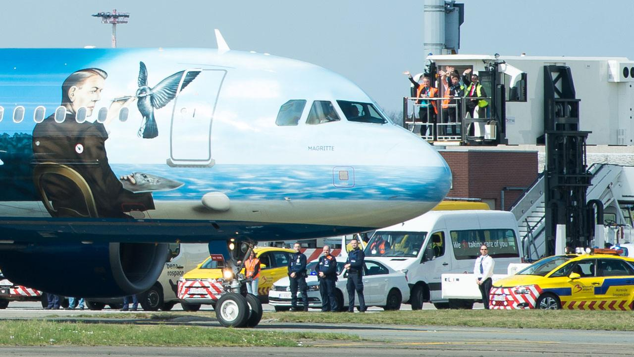 Airport workers wave as a Brussels Airlines plane taxis towards the runway at Brussels Airport, in Zaventem, Belgium, Sunday, April 3, 2016.