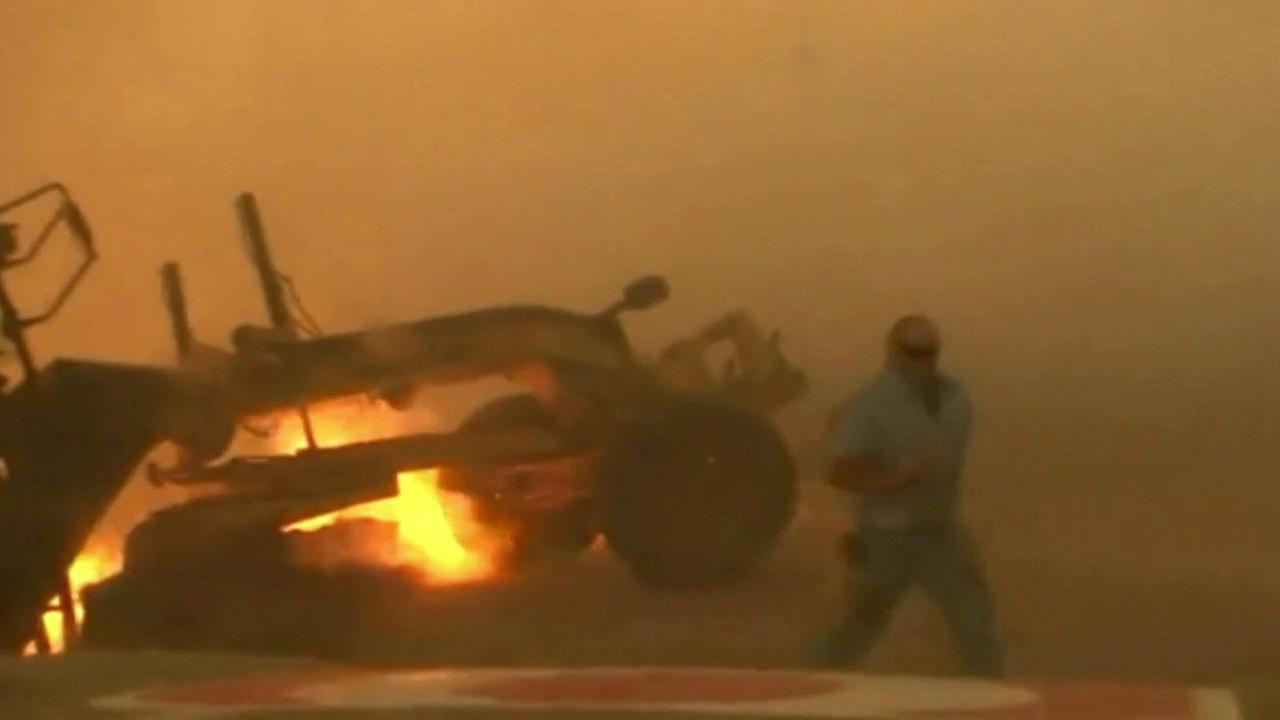 A man runs from his car after it was stuck on the side of a road in an Oklahoma wildfire.