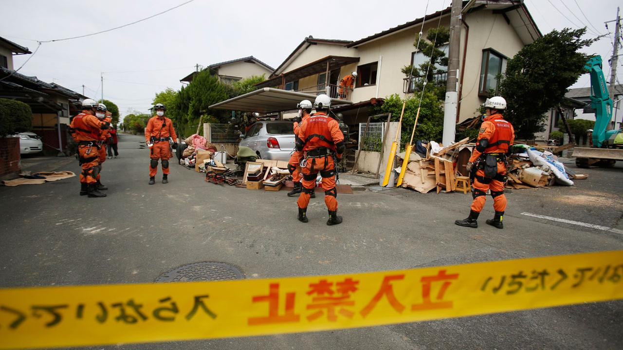 Rescue workers search for Yumiko Yamauchi, 93, at her collapsed house in Mashiki, Kumamoto prefecture, southern Japan, Saturday, April 16, 2016.