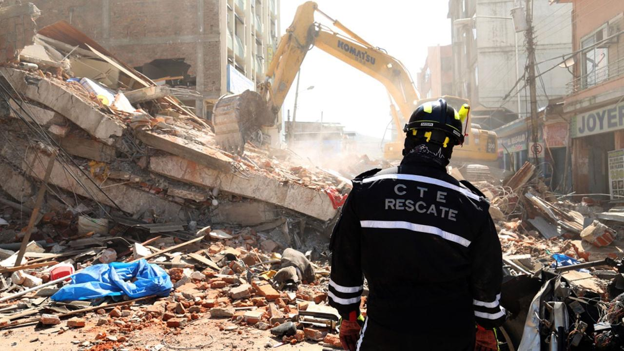 A rescue worker looks as heavy machinery removes the debris of a collapsed building in Portoviejo, Ecuador, Sunday April 17, 2016.