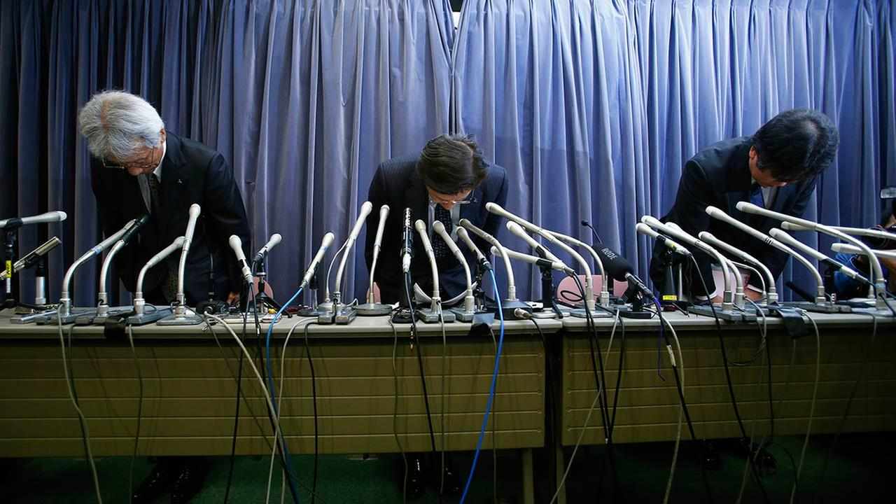 Mitsubishi Motors President Tetsuro Aikawa, center, bows in apology after a press conference in Tokyo where the company admitted falsifying fuel-mileage data.